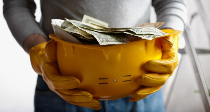 Construction hard hat filled with paper money