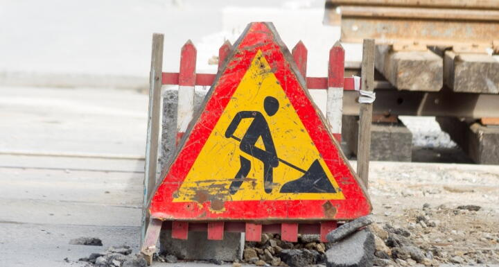 Construction utility sign on a cement pathway that is broken