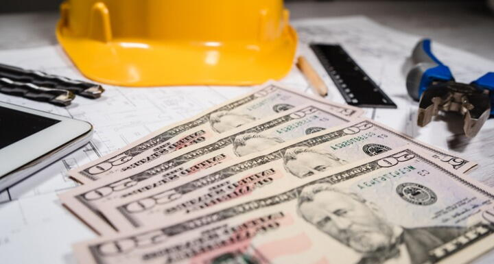 Yellow construction hat sitting on table with a layer of twenty dollar bills and a ruler and pencil