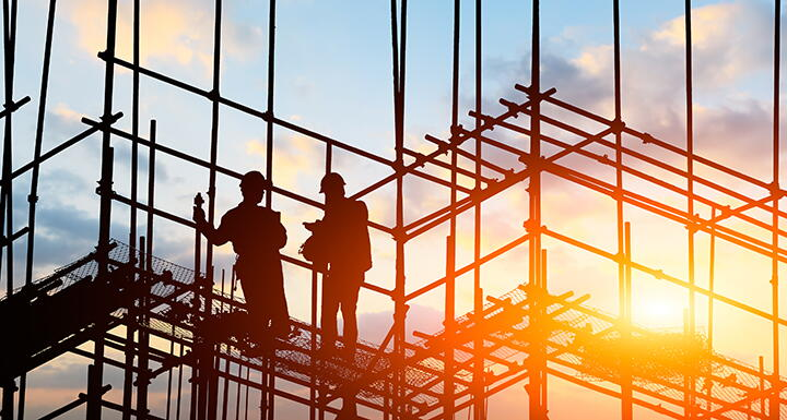 Silhouette of construction workers on frame of building