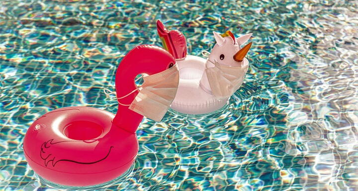 Two whimsical pool floats in a pool, with the floating characters wearing medical facemasks