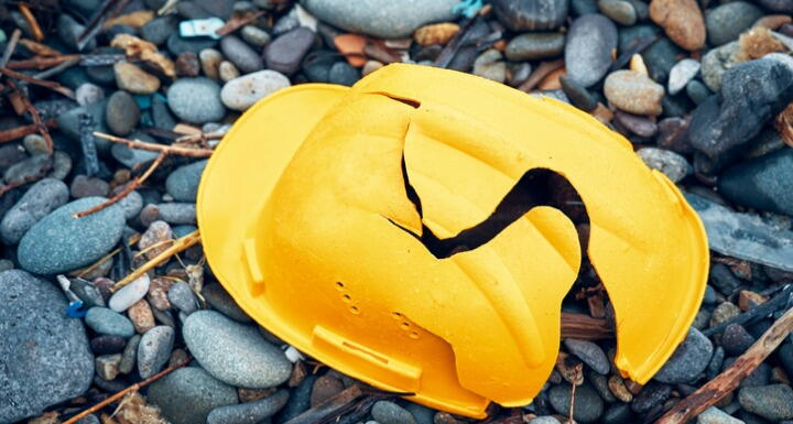 Cracked yellow construction helmet sitting on a bed of small stones