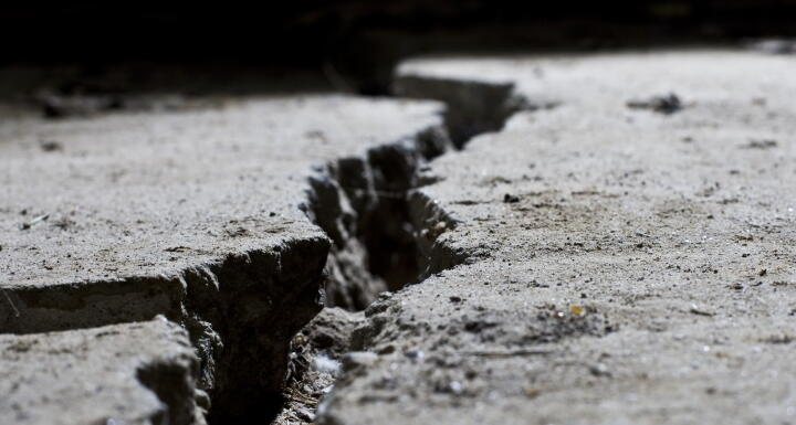 Concrete ground with large crack in running through it