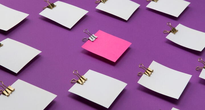 Pink post it note in the middle of white post it notes signifying standing out in a crowd