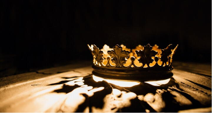 Gold crown sitting on a table with it's shadow reflecting on the table