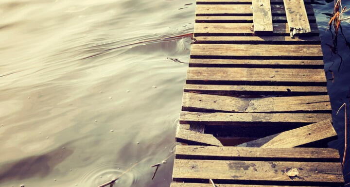 Pier over water with damaged boards