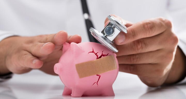 doctor examining cracked piggy bank with bandaid