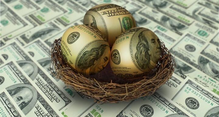 Egg shaped money in nest on top of hundred dollar bills