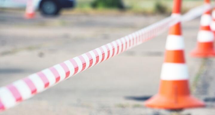 Orange construction cones and construction tape surround a lot