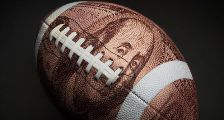 Football with $100 superimposed on its skin