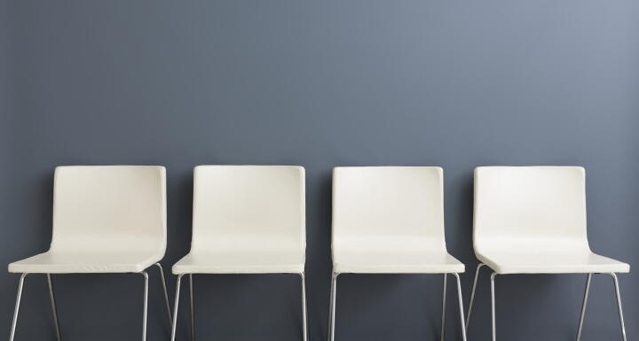 Four modern empty white chairs along a grey wall