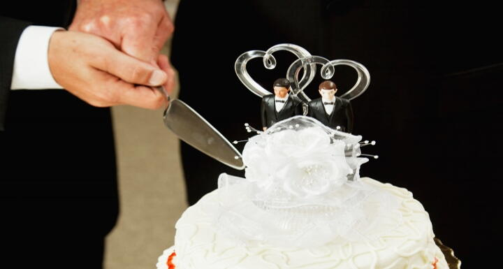 Two grooms cutting white, two-tiered wedding cake