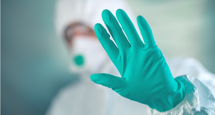 A medical professional wearing head to toe personal protective equipment with a gloved hand held up signaling to stop