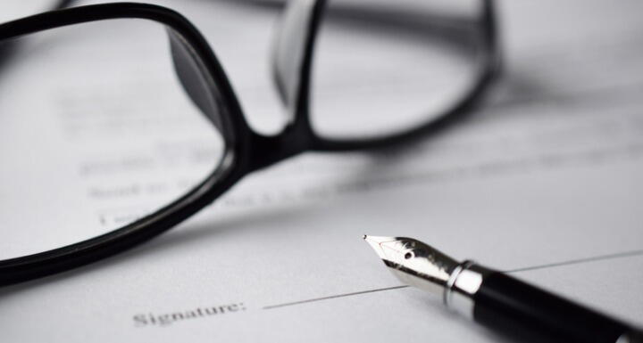 A pair of black glasses and fountain pen on top of a contract