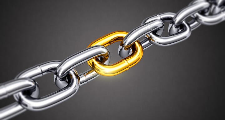 Gold link in a chain of silver links