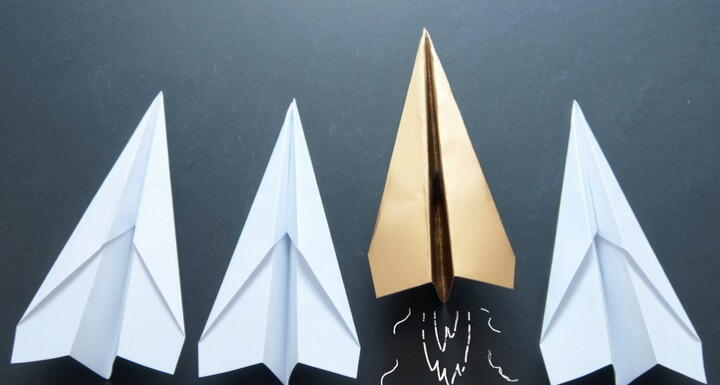 Gold paper airplane in between white paper airplanes