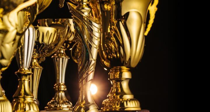 Golden trophies on black background