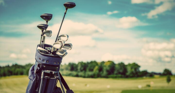 Golf bag filled with clubs sitting on golf course greens