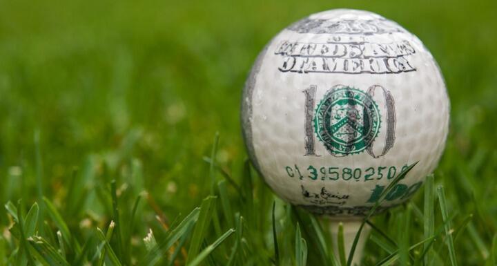 $100 bill printed on white golf ball sitting on tee