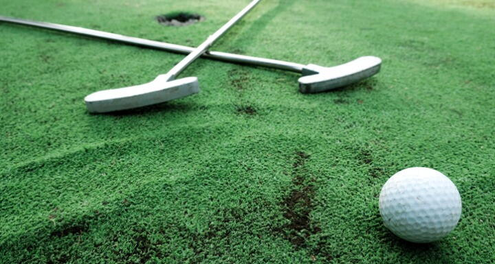 Golf clubs in cross shape with golf ball on green turf