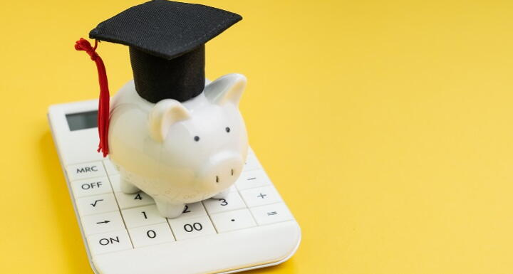 Illustration of a piggy bank wearing a graduation cap and tassel on top of a calculator