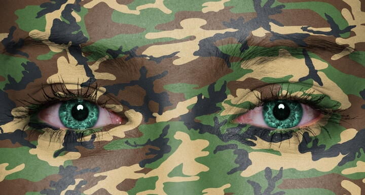 A face covered with green camouflage facepaint