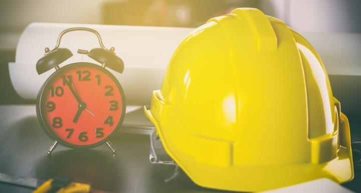 Yellow hard hat and alarm clock sitting on desk