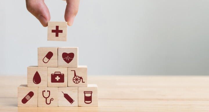 toy blocks with icons from health related disciplines arranged in a pyramid by an adult