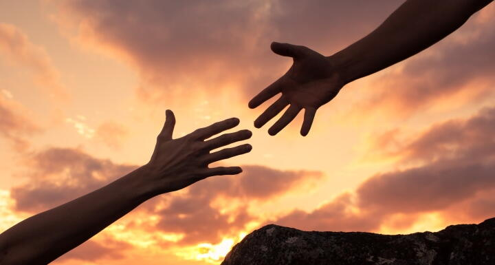 The hands of two people reaching for each other signifying helping hand