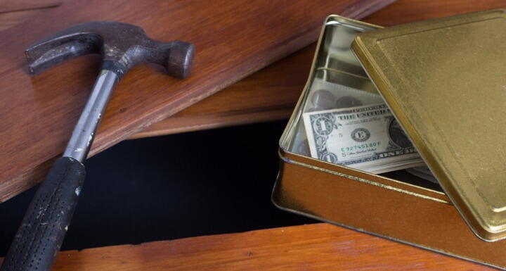 Money in a box with a hammer right beside a hole in a wooden floor