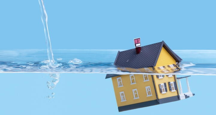 Distressed home with water rising above it