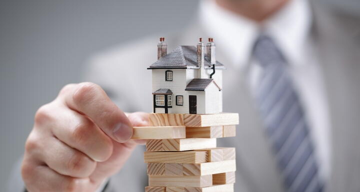 business man playing jenga with a toy house on the top of the puzzle