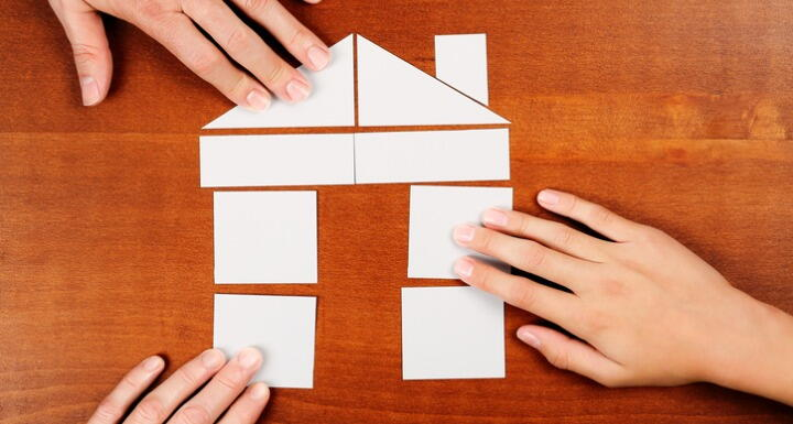3 hands putting together puzzle shaped as a house