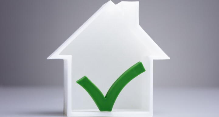 Small white house on a tabletop with a green check mark on the house