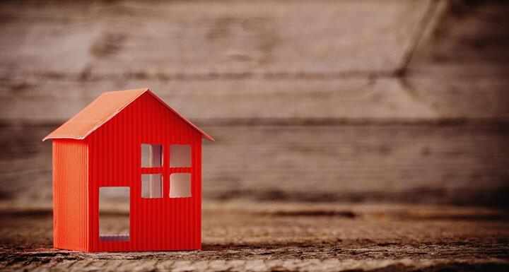 Orange 3D Paper House on wooden background