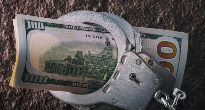 Hundred dollar bills in handcuffs