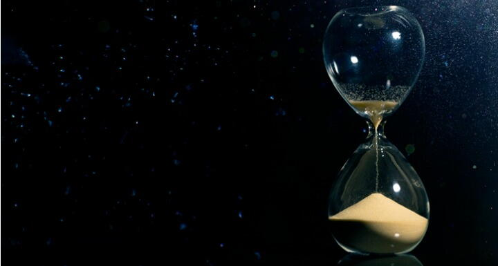An hourglass on a black background with grains of sand running through it