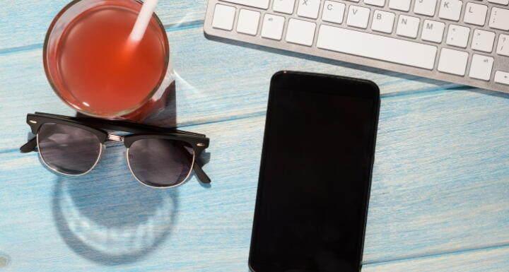 A orange drink, black sunglasses, a cellphone, and keyboard on blue table