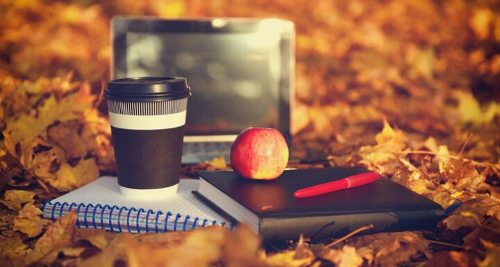 Laptop, apple, coffee, notepads, and pens surrounded by fall foliage