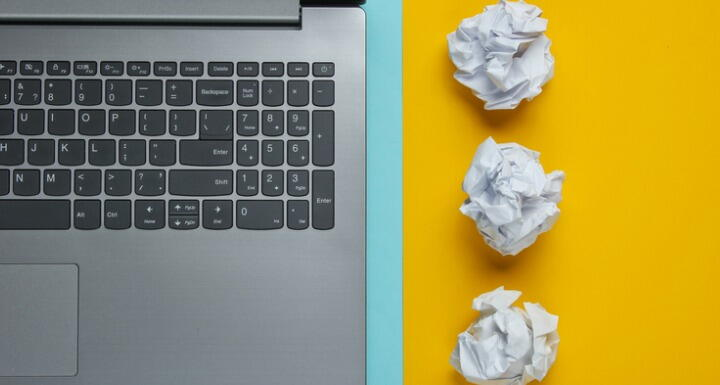 Laptop keyboard next to crumpled paper balls