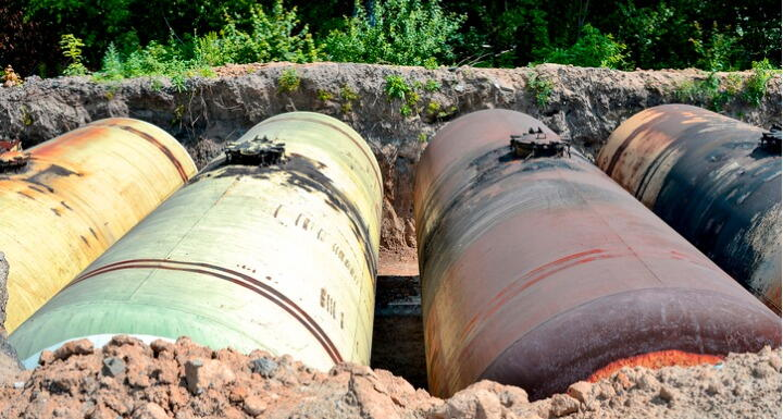 Large metal tanks are buried in the ground