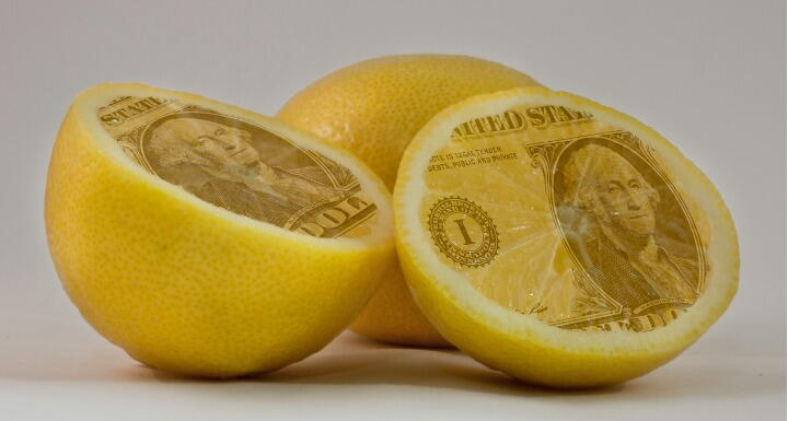 Lemons cut in half and the insides are the face of a dollar bill