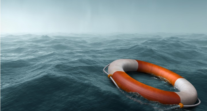 An orange and white life preserver floating on scary dark seas