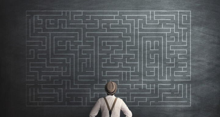 Man in hat and suspenders standing in front of a chalk board with an intricate maze written on it