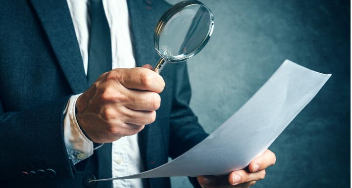 Man in a business suit holding a magnifying glass and reviewing a document
