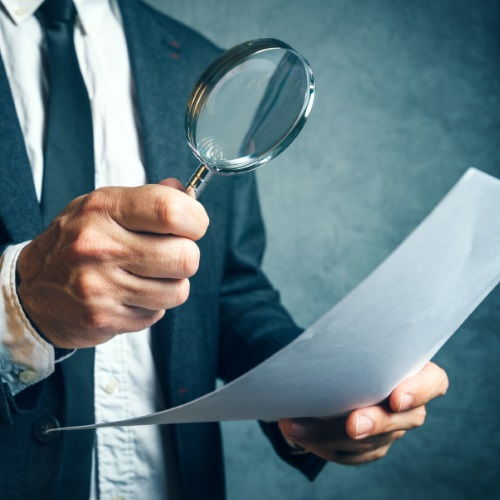 businessman inspecting paper with magnifying glass