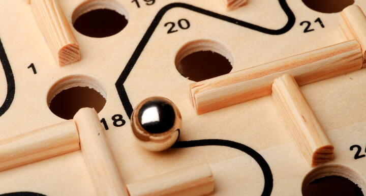 Maze game with a marble and holes in a game board