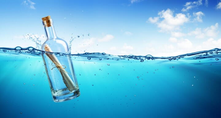 Message in a bottle floating in clear blue water with a clear blue sky in the background