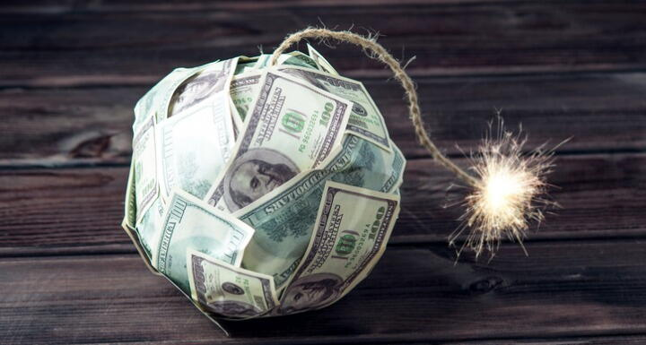 Ball of paper money shaped like a bomb with a rope as a fuse that is lit