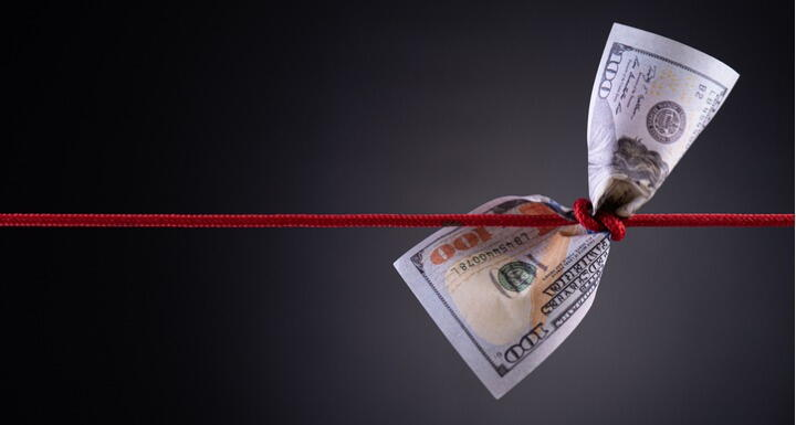 Paper money with red rope tied around the middle